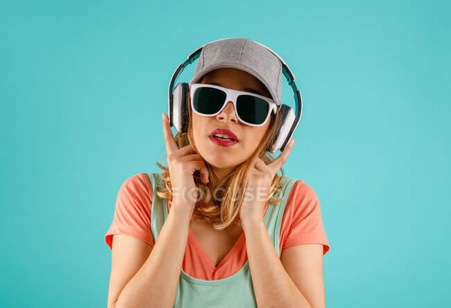 Giovane donna con occhiali da sole alla moda e cappuccio che tocca le cuffie e guarda la fotocamera mentre ascolta musica su sfondo turchese — Foto stock