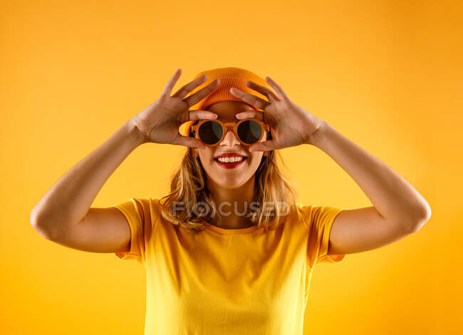 Happy young woman in bright clothes and stylish sunglasses smiling and looking at camera against orange background — Stock Photo