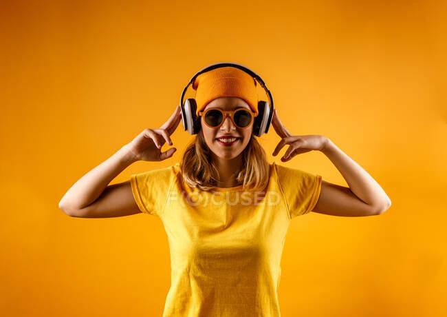 Mujer joven feliz en ropa brillante y gafas de sol elegantes sonriendo mirando a la cámara mientras escucha música sobre fondo naranja - foto de stock
