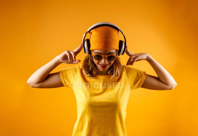 Happy young woman in bright clothes and stylish sunglasses smiling looking down while listening to music against orange background — Stock Photo