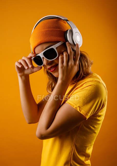 Счастливая барышня в яркой одежде, настраивая стильные солнечные очки и улыбаясь, слушая музыку на оранжевом фоне — стоковое фото