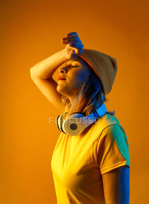 Красивая молодая женщина в оранжевом платье с наушниками на шее, с закрытыми глазами на оранжевом фоне — стоковое фото