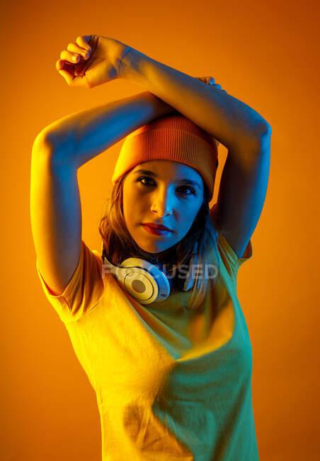 Уверенная стильная молодая женщина в оранжевом, то есть с наушниками на шее, держащая руку над головой и смотрящая на камеру на оранжевом фоне — стоковое фото