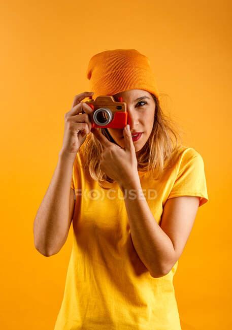 Счастливая молодая женщина смотрит в камеру, держа поддельную деревянную винтажную фотокамеру, стоящую на желтом фоне — стоковое фото