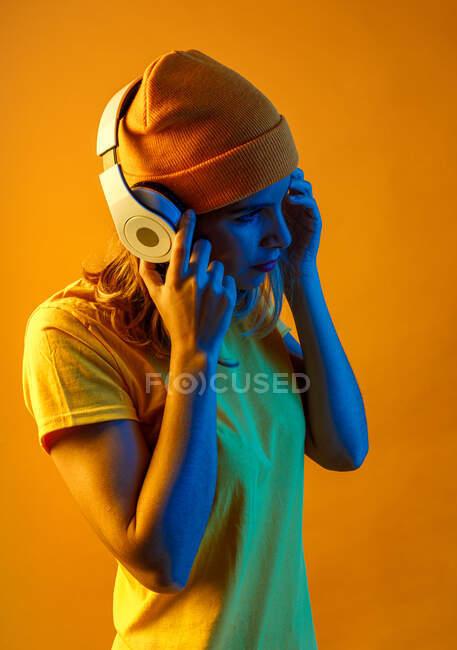 Vue latérale d'une jeune femme confiante et réfléchie en bonnet orange écoutant de la musique sur écouteurs regardant loin sur fond orange — Photo de stock