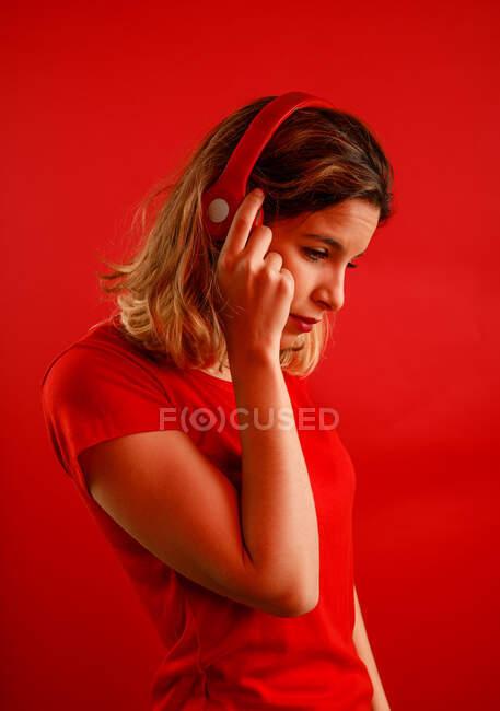 Вид сбоку счастливой молодой блондинки в ярких наушниках и футболке, улыбающейся и глядящей вниз, слушая музыку на красном фоне — стоковое фото