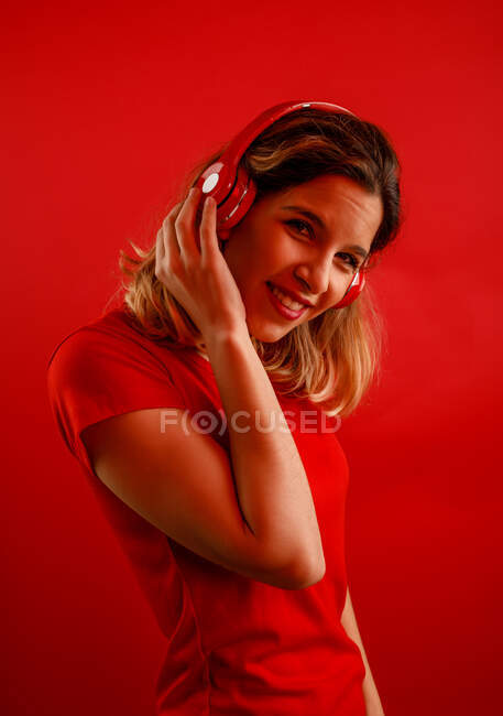 Side view of happy young blonde woman in vivid headphones and t shirt smiling and looking at camera while listening to music against red background — Stock Photo
