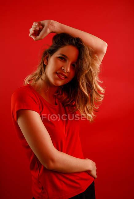 Mujer joven feliz sonriendo y mirando a la cámara mientras está de pie sobre el fondo rojo con el brazo sobre la cabeza - foto de stock