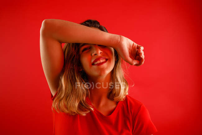 Happy young woman smiling and looking at camera while standing against red background with arm over the head — Stock Photo