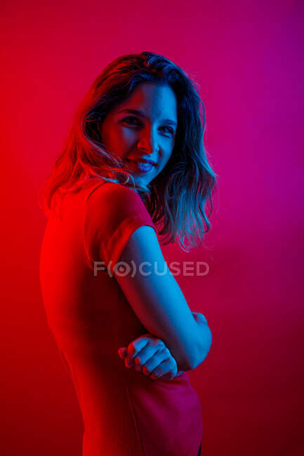 Side view of happy young woman with crossed arms smiling and looking at camera while standing under blue neon illumination against red background — Stock Photo