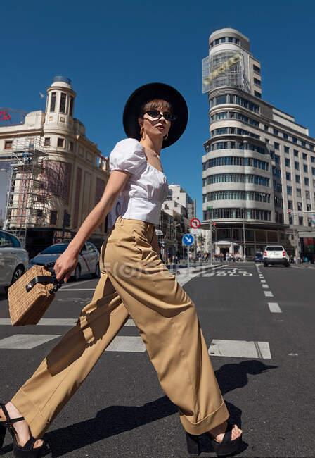 Dama de cuerpo entero en traje de moda caminando en el paso de peatones contra edificios y cielo despejado en día soleado en la calle de Madrid - foto de stock