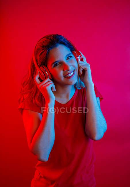 Joyeux jeune femme blonde dans des écouteurs vives et t-shirt souriant et regardant la caméra tout en écoutant de la musique sur fond rouge — Photo de stock