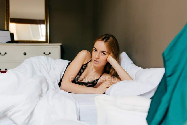 Довольно вдумчивая молодая женщина в нижнем белье лежит в постели и смотрит в камеру утром в уютной спальне дома — стоковое фото