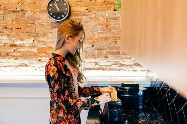 Уранці, готуючи сніданок на затишній кухні, можна побачити щасливу молоду жінку в квітковій блузці. — стокове фото