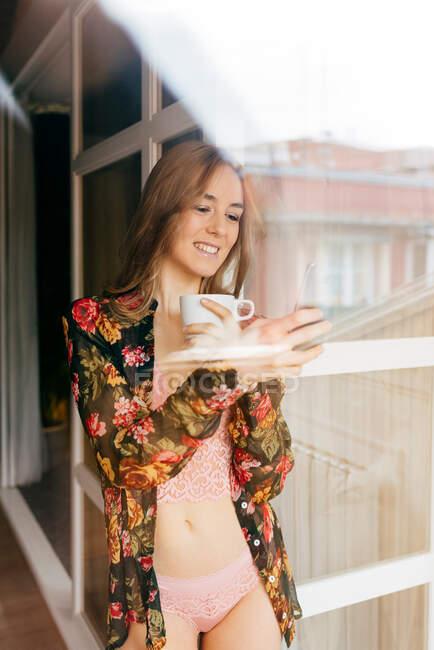 Счастливая привлекательная молодая женщина в стильном нижнем белье и цветном халате смотрит в окно, проводя утро за чашкой кофе и смартфоном дома — стоковое фото