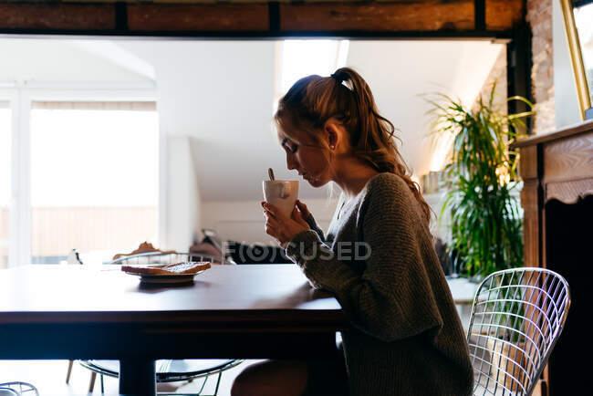 Vista lateral de jovem deprimida fêmea em desgaste casual sentado à mesa com xícara de café nas mãos enquanto toma café da manhã em solidão em casa — Fotografia de Stock