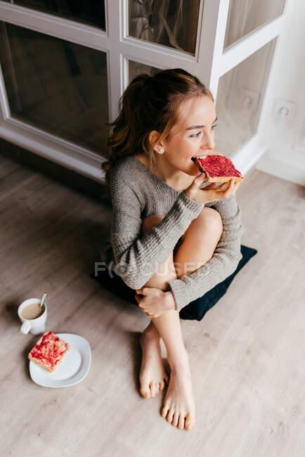 Сверху позитивная молодая женщина в повседневной одежде завтракает со сладким тостом и чашкой кофе, сидя на полу в комнате — стоковое фото