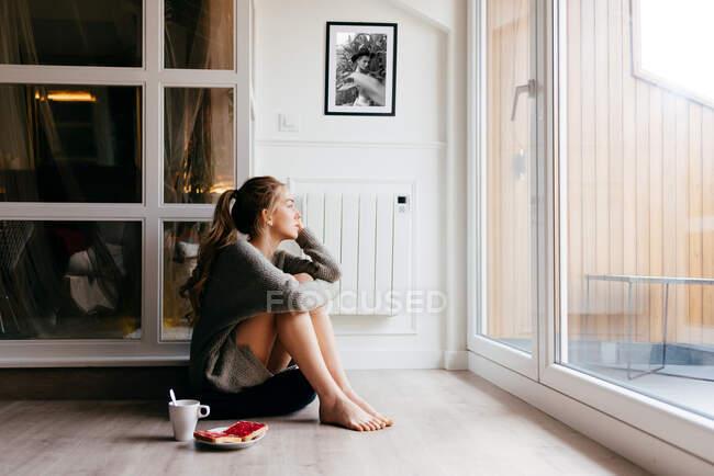 Спокійна молода жінка в повсякденному одязі, дивлячись на вікно задумливо, сидячи на підлозі з чашкою кави і тостів під час сніданку вдома. — стокове фото