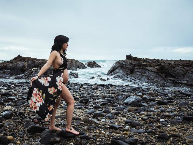 Вид сбоку на чувственную беременную женщину, смотрящую в сторону в длинном размахивающемся нижнем белье, идущую голым животом по скалистому побережью в мрачный день — стоковое фото