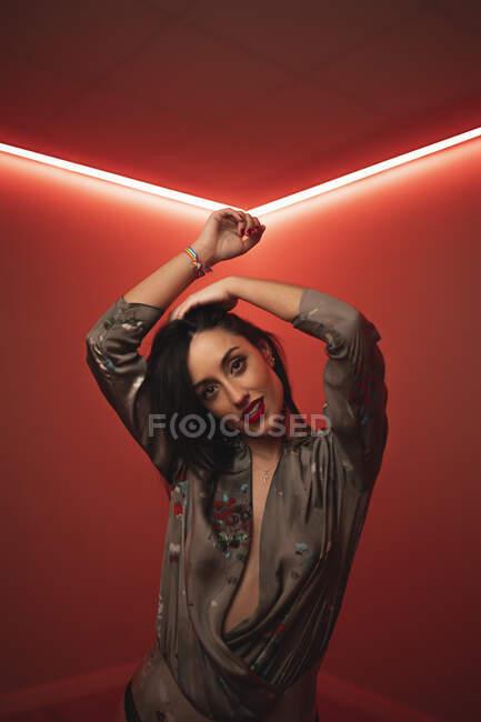 Femme brune sensuelle regardant la caméra en body élégant levant les bras et dansant dans la chambre avec éclairage au néon coloré — Photo de stock