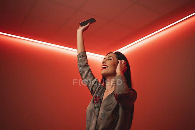 D'en bas heureuse femme à la mode avec les yeux fermés tenant smartphone dans les bras levés écoutant de la musique sur écouteurs et dansant dans la chambre avec un éclairage au néon rouge vif la nuit — Photo de stock