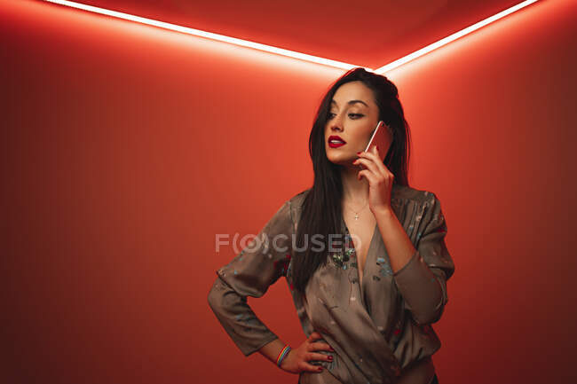 From below trendy woman using smartphone while standing with hand on hip looking away in room with bright red neon illumination at night club — Stock Photo