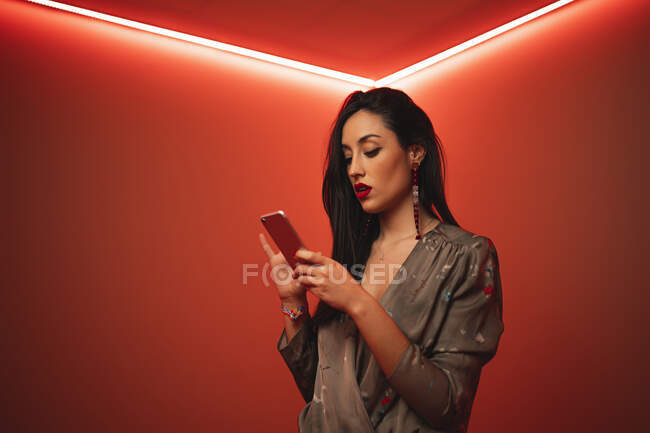 From below trendy woman using smartphone in room with bright red neon illumination at night club — Stock Photo