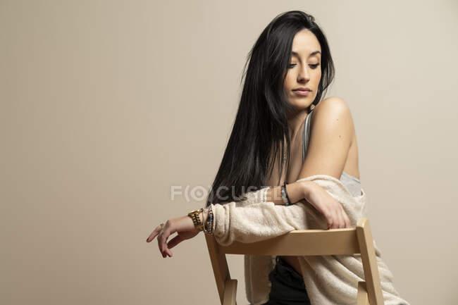 Молода Брюнет у повсякденному одязі, що сидить на стільці біля бежевої стіни. — стокове фото