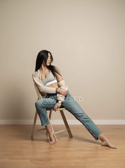 Plein corps petite brune jeune femme en tenue décontractée regardant dehors assise sur une chaise contre un mur beige — Photo de stock