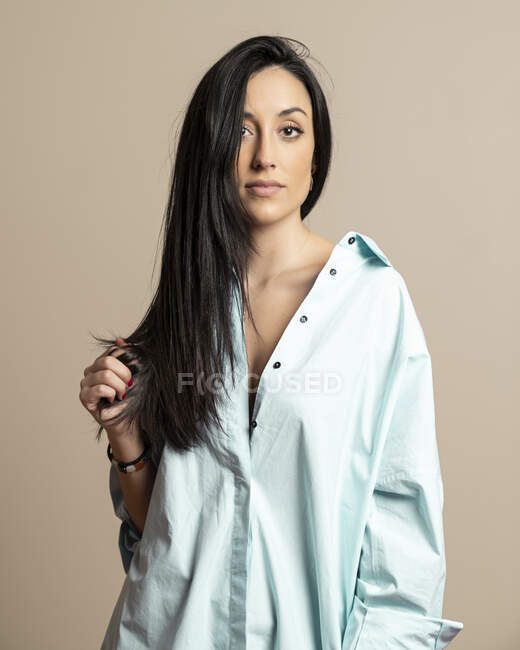 Beautiful brunette young woman in casual blue shirt looking at camera standing against beige wall — Stock Photo