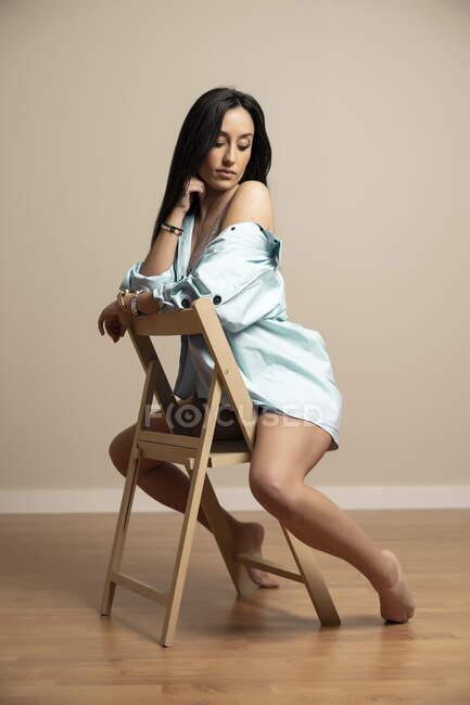 Полный вид тела стройная брюнетка молодая женщина в синей рубашке смотрит вниз с закрытыми глазами сидя на стуле против бежевой стены — стоковое фото