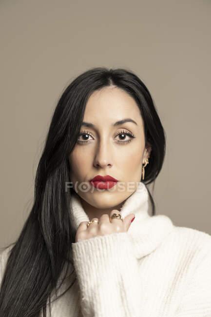 Attraente donna bruna in elegante maglione guardando la fotocamera con rossetto rosso su sfondo beige — Foto stock