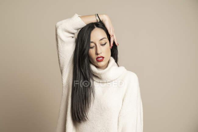 Attraente donna bruna in elegante maglione con gli occhi chiusi che tengono i capelli sullo sfondo beige — Foto stock