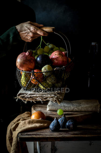 Crop senior person taking fruit from basket — Stock Photo