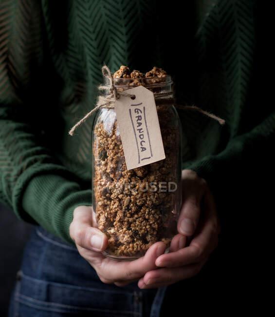Pot en verre féminin méconnaissable de millet frais et de granola de quinoa avec étiquette — Photo de stock