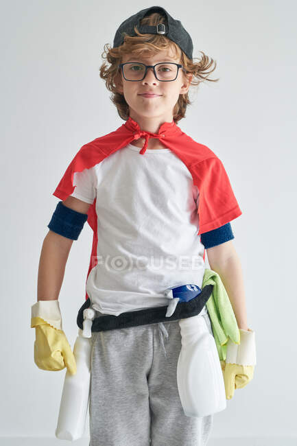 Confident boy in superhero cape with detergents looking at camera against gray background — Stock Photo