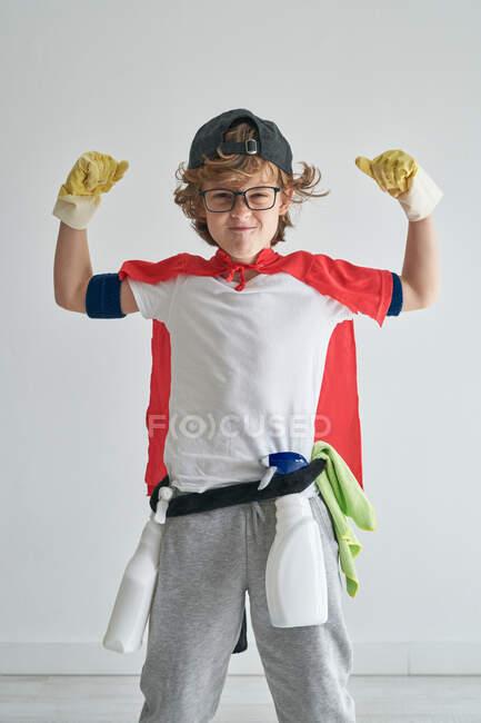Веселый мальчик в костюме супергероя с моющим средством и губкой, сгибающей мышцы и улыбающийся перед камерой во время уборки квартиры — стоковое фото