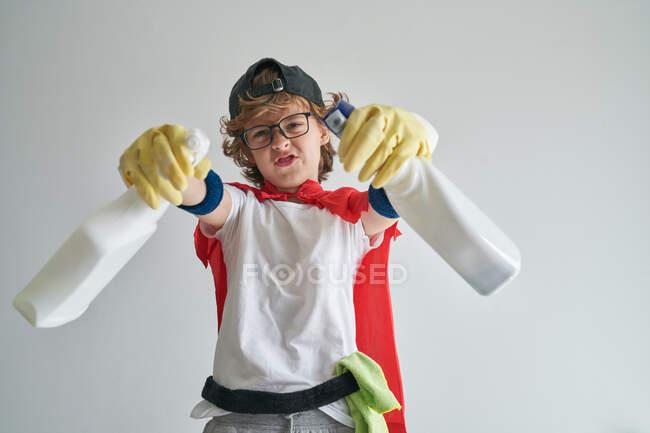 Engraçado menino feliz em capa de super-herói e óculos de pulverização câmera com detergente enquanto arrumando apartamento contra fundo cinza — Fotografia de Stock