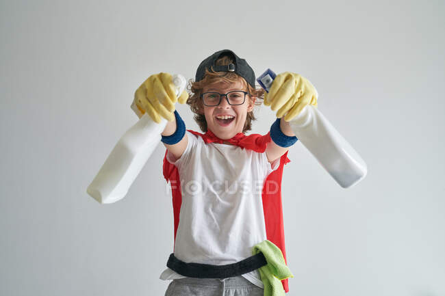 Funny happy little boy in superhero cape and glasses spraying camera with detergent while tidying apartment against gray background — Stock Photo