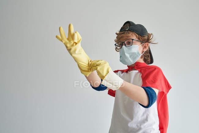 Мальчик в костюме супергероя и медицинской маске надевает желтые резиновые перчатки, прежде чем провести дезинфекцию на их фоне — стоковое фото
