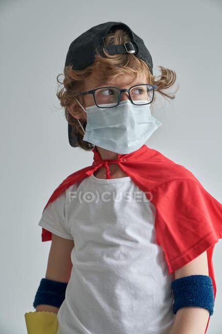Garçon en costume de super-héros et masque médical debout regardant fièrement loin tout en rangeant appartement moderne — Photo de stock