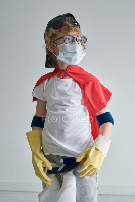 Boy in superhero costume and medical mask standing proudly looking away while tidying modern apartment — Stock Photo