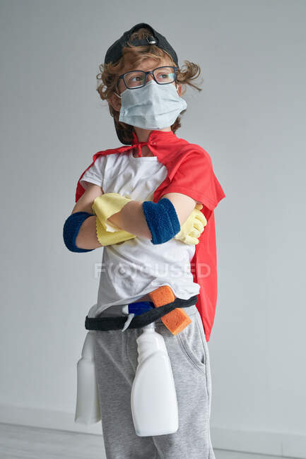 Boy in superhero costume and medical mask standing proudly with cross arms and looking away while tidying modern apartment — Stock Photo