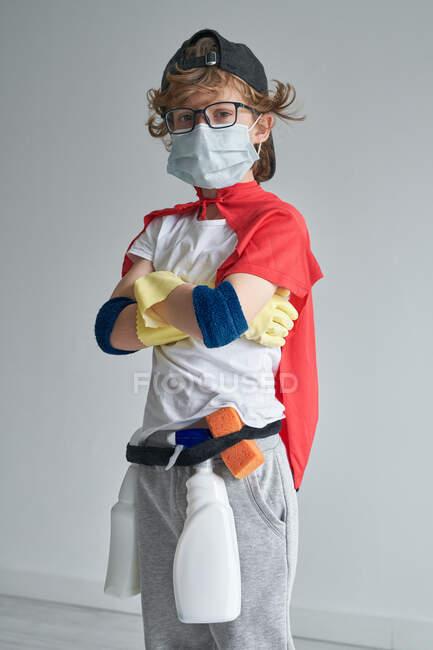Хлопчик у костюмі супергероя та медична маска з гордістю стоять з перехресними руками і дивляться на камеру під час освоєння сучасної квартири. — Stock Photo
