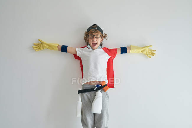 Happy boy in superhero costume and with detergents leaning on gray wall with outstretched arms while cleaning apartment — Stock Photo