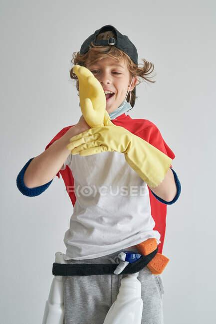 Ragazzino in costume da supereroe guardando la fotocamera che gioca con il guanto di gomma soffiato mentre pulisce l'appartamento sullo sfondo grigio — Foto stock