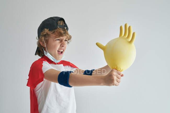 Petit garçon drôle en cape de super-héros jouant avec un gant en caoutchouc gonflé tout en effectuant la désinfection sur fond gris — Photo de stock