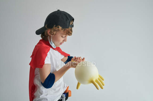 Funny little boy in superhero cape playing with inflated rubber glove while performing disinfection against gray background — Stock Photo