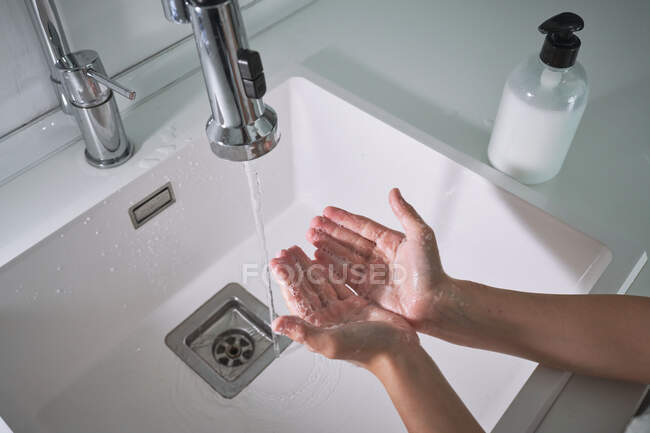 From above top view cropped unrecognizable child boy washing hands under running water carefully in modern bathroom at home — Stock Photo