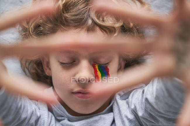 Top view of boy with colorful rainbow under eye with eyes closed showing stop gesture with hands with stay home inscription to the camera while lying on pillow and blanket on floor — Stock Photo